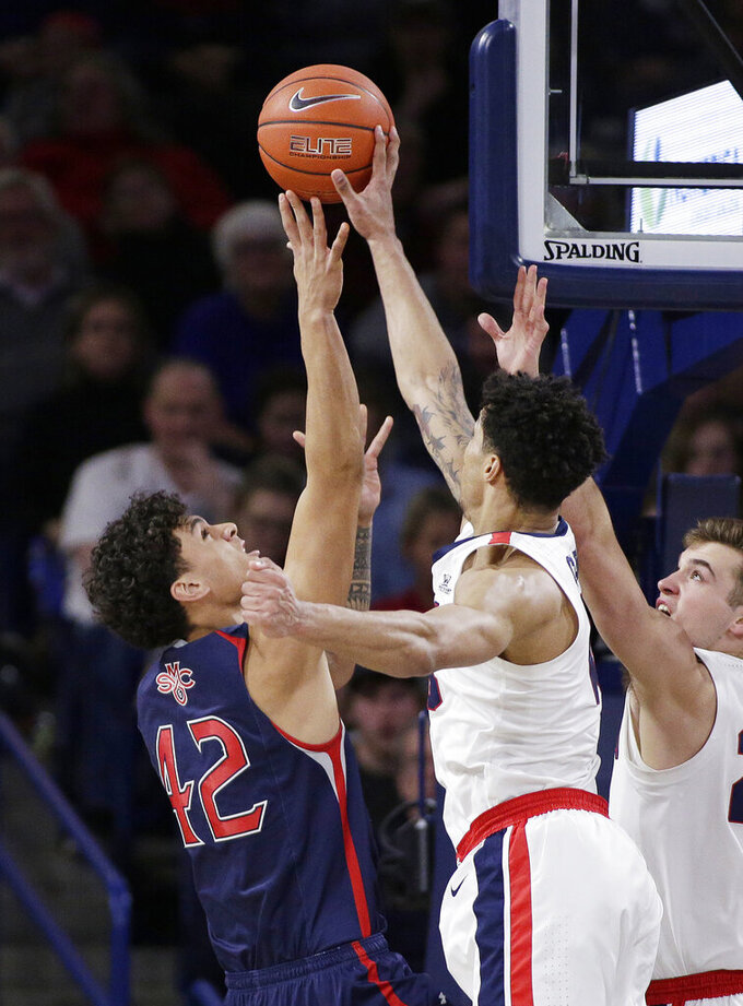 Gonzaga forward Brandon Clarke, center, blocks a shot by Saint Mary's forward Dan Fotu, left, in front of Gonzaga forward Corey Kispert during the first half of an NCAA college basketball game in Spokane, Wash., Saturday, Feb. 9, 2019. (AP Photo/Young Kwak)