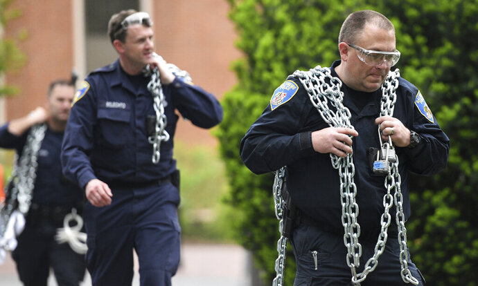 Baltimore Police carry chains that protesters had used during a monthlong sit-in at Garland Hall on Johns Hopkins' Homewood campus, Wednesday, May 8, 2019. Baltimore police arrested seven people as they ended a monthlong sit-in in the lobby of an administrative building at Johns Hopkins University, where protesters have demonstrated against the creation of a campus police force and the institution's contracts with the U.S. Immigrations and Customs Enforcement agency. (Jerry Jackson/The Baltimore Sun via AP)