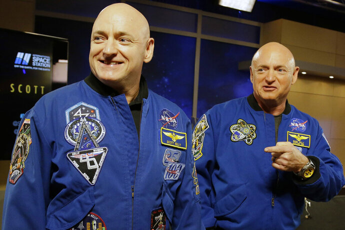FILE - In this March 4, 2016 file photo, NASA astronaut Scott Kelly, left, and his identical twin, Mark, stand together before a news conference in Houston. From his eyes to his immune system, Scott's body sometimes reacted strangely to nearly a year in orbit, at least compared to his Earth-bound brother _ but  research published on Thursday, April 11, 2019 shows nothing that would cancel even longer space treks, like to Mars. (AP Photo/Pat Sullivan, File)