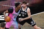 Brooklyn Nets' Joe Harris (12) defends against Miami Heat's Bam Adebayo (13) during the second half of an NBA basketball game Saturday, Jan. 23, 2021, in New York. (AP Photo/Frank Franklin II)