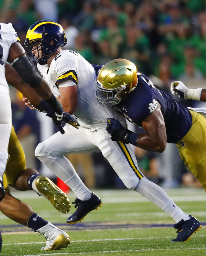 FILE - In this Sept. 1, 2018, file photo, Notre Dame defensive lineman Khalid Kareem (53) sacks Michigan quarterback Shea Patterson (2) in the first half of an NCAA football game in South Bend, Ind. Notre Dame junior Khalid Kareem found himself lost in the defensive line shuffle for most of his first two seasons with the Irish. Always buried on the depth chart, the Detroit native just wanted a chance to prove that he could become a regular contributor, and perhaps even a starter. A late-season surge in 2017 followed by a stellar showing in spring ball earned Kareem his chance at both. (AP Photo/Paul Sancya)