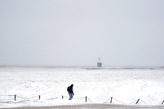 A lone man walks along a frozen section of North Ave. beach on Lake Michigan north of downtown Chicago Tuesday, Jan. 26, 2021. A major winter storm dumped more than a foot of snow on parts of the middle of the country stretching from central Kansas northeast to Chicago and southern Michigan.(AP Photo/Charles Rex Arbogast)