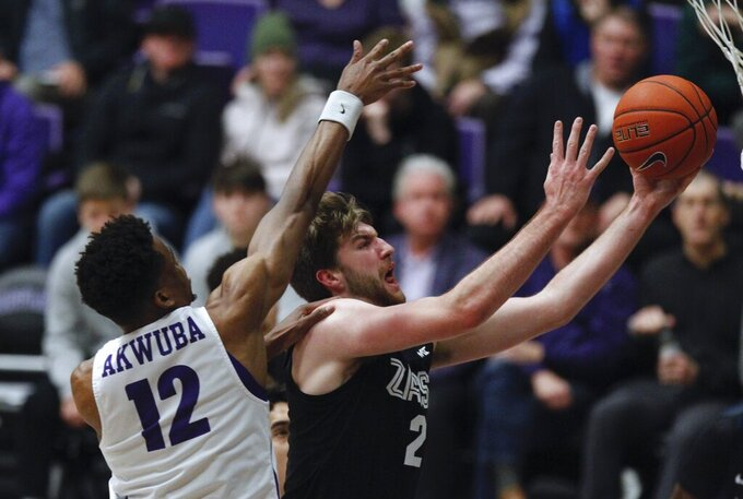 Portland center Theo Akwuba, left, defends as Gonzaga forward Drew Timme, right, shoots during the first half of an NCAA college basketball game in Portland, Ore., Thursday, Jan. 2, 2020. Gonzaga won  85-72. (AP Photo/Steve Dipaola)