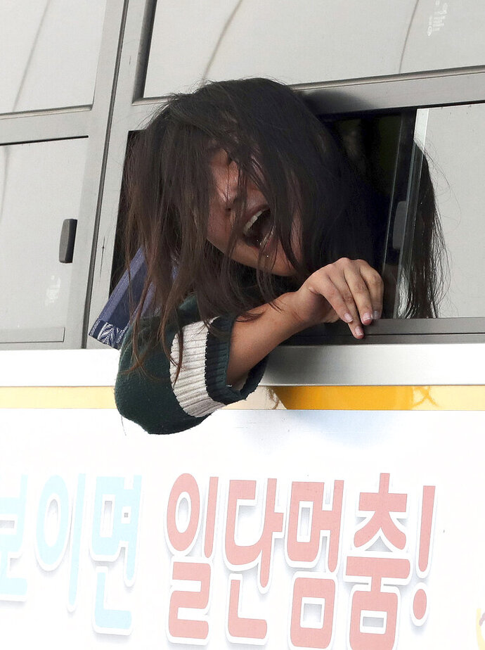 In this Friday, Oct. 18, 2019, photo, a detained college student shouts a slogan into a police bus in front of the U.S. ambassador's residence in Seoul, South Korea. South Korean police said Saturday, Oct. 19, they beefed up security at the U.S. ambassador's residence in Seoul after a group of anti-American students used ladders to break into the compound. The sign reads