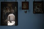 Pilgrim Nikos Katseris, 19, is reflected in an icon as he crawls at the entrance of the Holy Church of Panagia of Tinos, on the Aegean island of Tinos, Greece, on Thursday, Aug. 13, 2020. For nearly 200 years, Greek Orthodox faithful have flocked to Tinos for the August 15 feast day of the Assumption of the Virgin Mary, the most revered religious holiday in the Orthodox calendar after Easter. But this year there was no procession, the ceremony _ like so many lives across the globe _ upended by the coronavirus pandemic. (AP Photo/Thanassis Stavrakis)