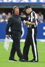 Oakland Raiders head coach Jon Gruden talks with head linesman Derick Bowers (74) during the first half of an NFL football game against the Indianapolis Colts in Indianapolis, Sunday, Sept. 29, 2019. (AP Photo/AJ Mast)