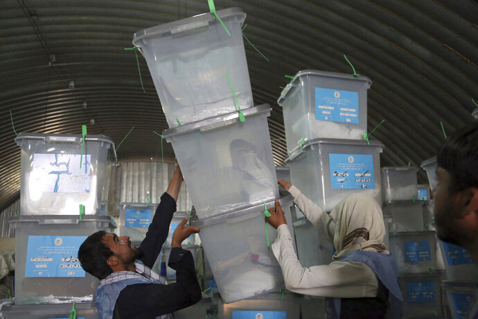 Afghan election workers stack ballot boxes at the warehouse of Afghanistan's Independent Election Commission in Kabul, Afghanistan, Sunday, Sept. 29, 2019. Presidential elections are over, and Afghanistan faces possible political chaos amid allegations of power abuse and a disorganized, sloppy voting process. A final tally is only expected Nov. 7, deepening uncertainty. (AP Photo/Rahmat Gul)