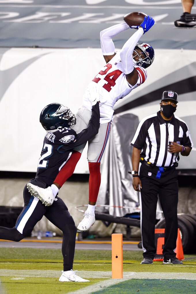 New York Giants' James Bradberry (24) intercepts a pass against Philadelphia Eagles' John Hightower (82) during the first half of an NFL football game, Thursday, Oct. 22, 2020, in Philadelphia. (AP Photo/Derik Hamilton)