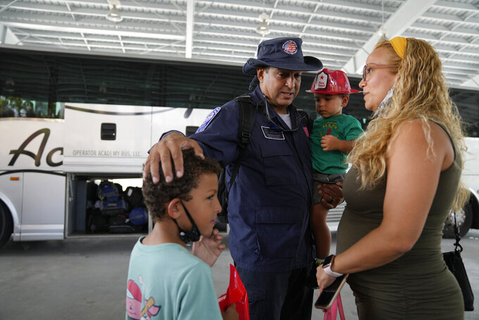 Enrique Calvo greets his sons Alec, 6, Enrique, 2, and wife Joceline, as members of Miami-Dade Fire Rescue's urban search and rescue team are reunited with their families after weeks of working on the rubble pile at the collapsed Champlain Towers South condominium, on Friday, July 23, 2021, in Doral, Fla. (AP Photo/Rebecca Blackwell)