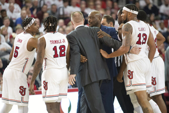 St. John's head coach Chris Mullin, center, is assisted off the court by the players after receiving a technical foul in the second half of an NCAA college basketball game against the DePaul , Saturday, Jan. 12, 2019, in New York. DePaul won 79-71. (AP Photo/Mary Altaffer)