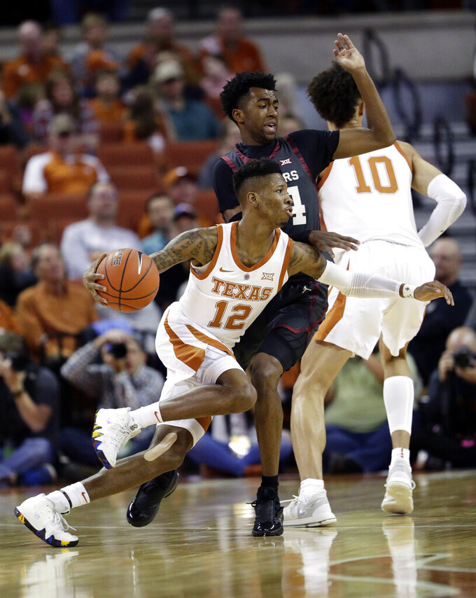 Texas guard Kerwin Roach II (12) drives around Oklahoma guard Jamal Bieniemy (24) during the first half of an NCAA college basketball game, in Austin, Texas, Saturday, Jan. 19, 2019. (AP Photo/Eric Gay)
