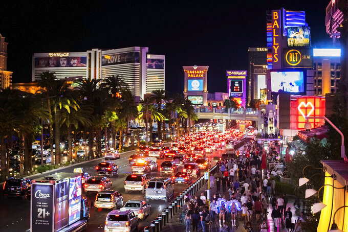 FILE - In this March 19, 2021, file photo, vehicles and crowds move along the strip in Las Vegas. One big casino operator says it'll begin charging parking fees again at events and its Las Vegas Strip resorts. The move by MGM Resorts International marks the end of free parking that lingered after pandemic-related casino shutdowns. In a statement on Tuesday, May 11, 2021, the company cited signs of economic recovery and increasing numbers of guests. (Benjamin Hager/Las Vegas Review-Journal via AP, File)