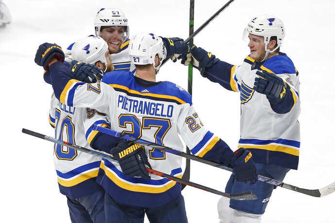 St. Louis Blues' Ryan O'Reilly, left, is congratulated by teammates after scoring in overtime of the team's NHL hockey game against the Minnesota Wild on Saturday, Nov. 2, 2019, in St. Paul, Minn. The Blues won 4-3. (AP Photo/Jim Mone)