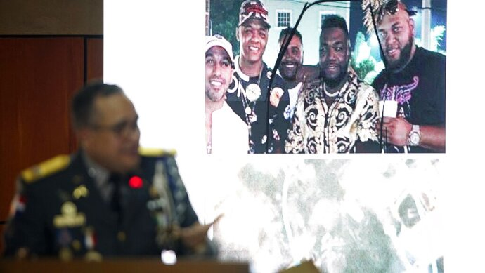 Director of the National Police, General Ney Aldrin Bautista Almonte, projects a photograph taken of former Boston batter David Ortiz, second from right, with others on the night he was shot in Santo Domingo, Dominican Republic, Wednesday June 19, 2019. According to Bautista Almonte, Ortiz was shot by a gunman who mistook him for the real target, Sixto David Fernández, not in the projected photo, who was seated at the same table with the former baseball star on the night of June 9. (AP Photo/Roberto Guzman)