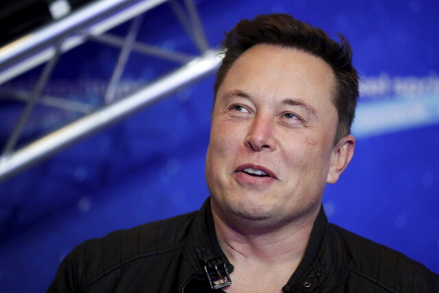 FILE - In this Tuesday, Dec. 1, 2020, file photo, SpaceX owner and Tesla CEO Elon Musk arrives on the red carpet for the Axel Springer media award, in Berlin. In a tweet Tuesday, Dec. 22, 2020, Musk said he once considered selling the electric car maker to Apple, but the iPhone maker's CEO Tim Cook blew off the meeting. (Hannibal Hanschke/Pool Photo via AP, File)