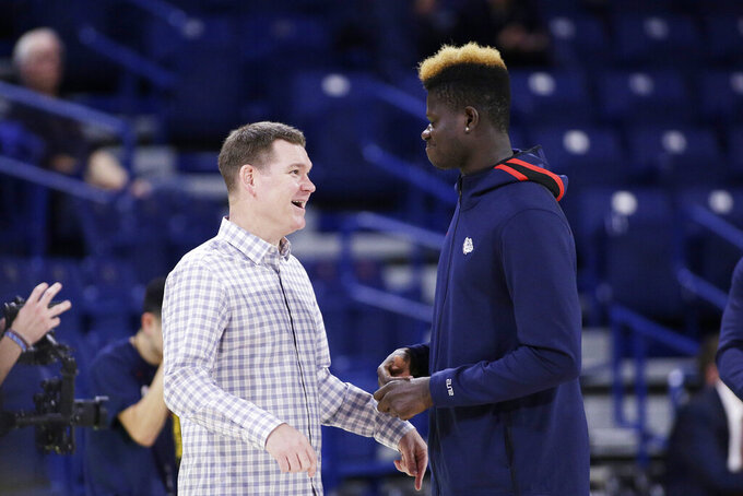 FILE - In this Nov. 5, 2019, file photo, Gonzaga assistant coach Tommy Lloyd, left, and academic redshirt Oumar Ballo, of Mali, speak before an NCAA college basketball game against Alabama State in Spokane, Wash. Lloyd's passports is rich with stamps. In his 19th season as Few's top assistant at second-ranked Gonzaga, Lloyd has become the conduit for the Zags' international expansion. (AP Photo/Young Kwak, File)