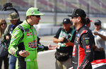 FILE - Kyle Busch, left, talks with his brother Kurt Busch before qualifications for a NASCAR Cup Series auto race at Michigan International Speedway in Brooklyn, Mich., in this Friday, Aug. 10, 2018, file photo.  The Busch brothers are moving up on the Allisons on NASCAR's all-time wins list for siblings. (AP Photo/Paul Sancya, File)