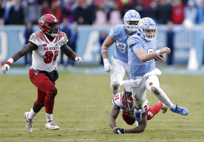 North Carolina quarterback Cade Fortin (6) runs the ball as North Carolina State's Jarius Morehead (31) and Stephen Griffin (21) chase during the first half of an NCAA college football game in Chapel Hill, N.C., Saturday, Nov. 24, 2018. (AP Photo/Gerry Broome)