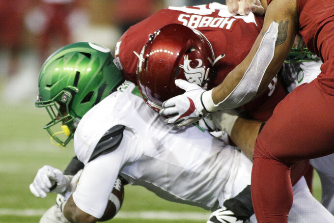 Washington State defensive lineman Dallas Hobbs, top, tackles Oregon running back CJ Verdell during the second half of an NCAA college football game in Pullman, Wash., Saturday, Nov. 14, 2020. Oregon won 43-29. (AP Photo/Young Kwak)