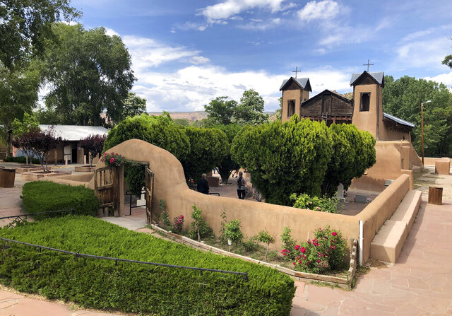 In this June 16, 2019 photo El Santuario de Chimayó is shown in Chimayó, N.M. El Santuario de Chimayó is known around the world for its healing sand and is the northern New Mexico shrine where believers ask for mercy and miracles to stage off sickness and death. But with the outbreak of the novel coronavirus, the sanctuary is one of many Hispanic Catholic sites around the country closing and limiting access to pilgrims seeking a last hope prayer. (AP Photo/Russell Contreras)