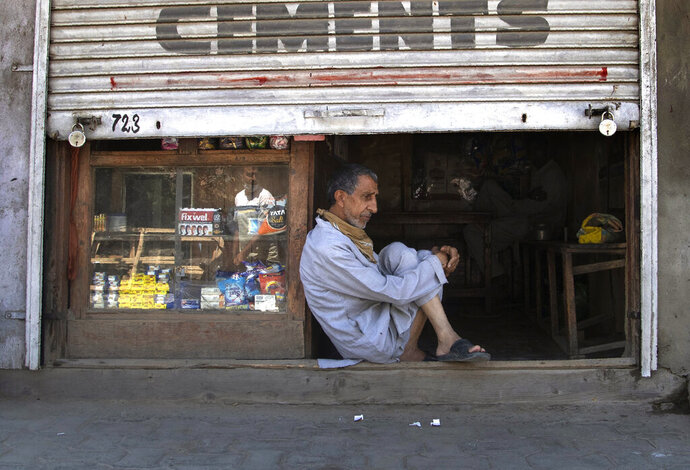 A Kashmiri shopkeeper sits at the entrance of his half closed shop during lockdown in Srinagar, Indian controlled Kashmir, July 27, 2020. Indian-controlled Kashmir's economy is yet to recover from a colossal loss a year after New Delhi scrapped the disputed region's autonomous status and divided it into two federally governed territories. (AP Photo/Mukhtar Khan)