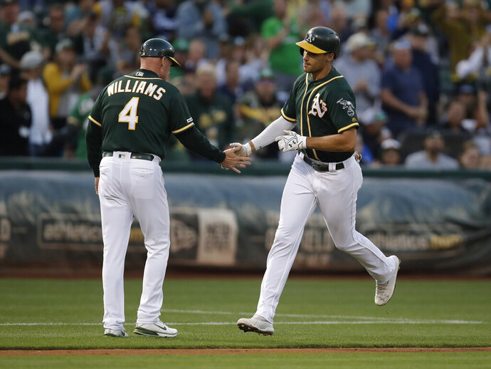Oakland Athletics' Matt Olson, right, is congratulated by third base coach Matt Williams after hitting a two-run home run off New York Yankees pitcher Domingo German during the first inning of a baseball game Tuesday, Aug. 20, 2019, in Oakland, Calif. (AP Photo/Ben Margot)