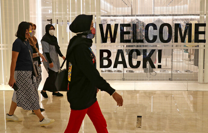 Visitors wearing protective masks walk through the Senayan City shopping mall during its reopening after being closed for weeks due to the large-scale restrictions imposed to curb the spread of the new coronavirus outbreak, in Jakarta, Indonesia, Monday, June 15, 2020. As Indonesia's overall virus caseload continues to rise, the capital city has moved to restore normalcy by lifting some restrictions, saying that the spread of the virus in the city of 11 million has slowed after peaking in mid-April. (AP Photo/Tatan Syuflana)