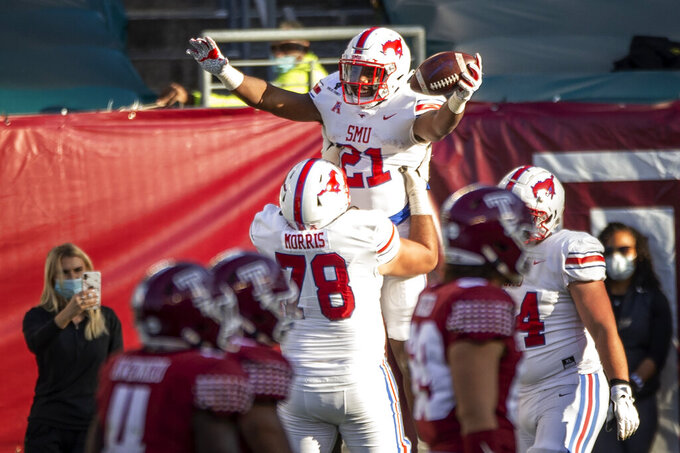 SMU running back TaMerik Williams (21) is lifted by offensive lineman Beau Morris (78) after scoring a touchdown during the second half of an NCAA college football game against Temple, Saturday, Nov. 7, 2020, in Philadelphia. SMU won 47-23. (AP Photo/Laurence Kesterson)