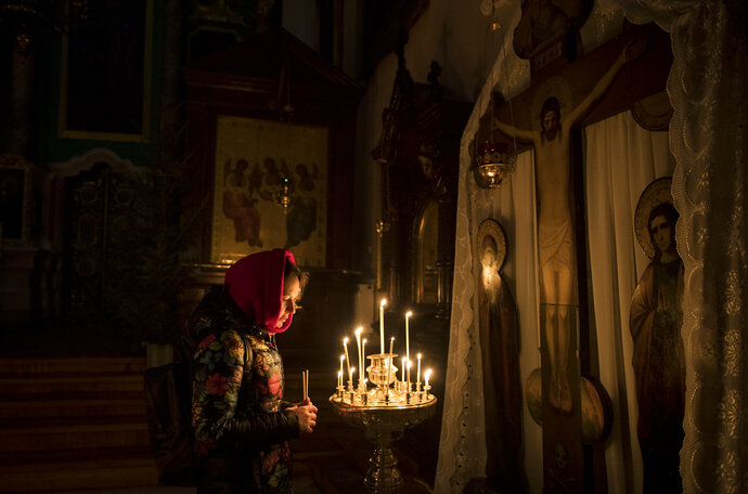 A Lithuanian Orthodox worshipper lights candles on Orthodox Christmas Eve in the Prechistensky, the Cathedral Palace in Vilnius, Lithuania, on Saturday, Jan. 6, 2018. (AP Photo/Mindaugas Kulbis)