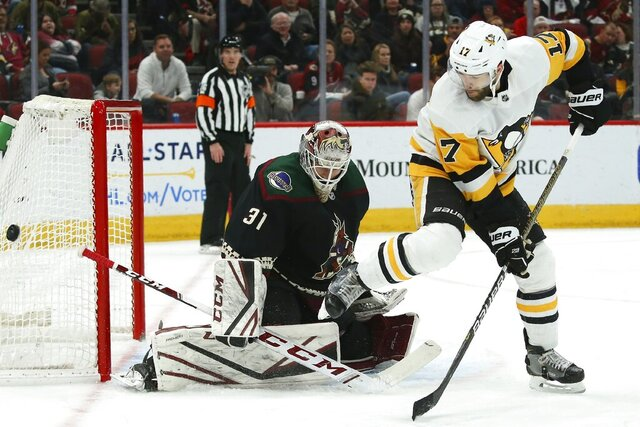 Arizona Coyotes goaltender Adin Hill (31) makes a save on a shot as Pittsburgh Penguins right wing Bryan Rust (17) gets out of the way of the shot during the second period of an NHL hockey game Sunday, Jan. 12, 2020, in Glendale, Ariz. (AP Photo/Ross D. Franklin)