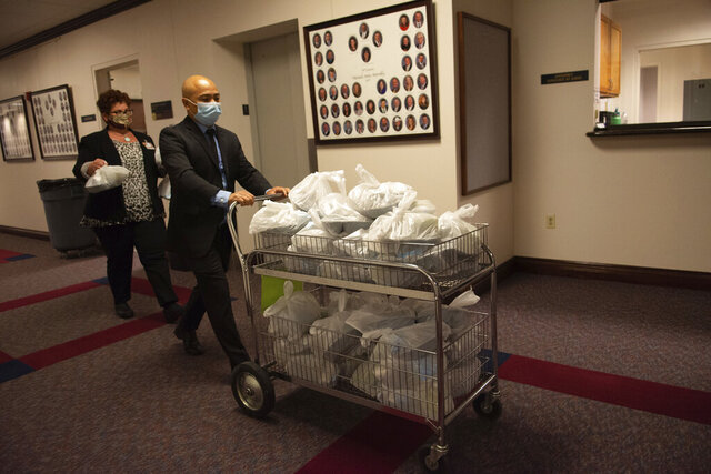 Assembly sergeants at arms bring lunch into the chambers on the second day of the 31st Special Session of the Nevada Legislature in Carson City, Nev., on Thursday, July 9, 2020. (David Calvert/The Nevada Independent via AP, Pool)
