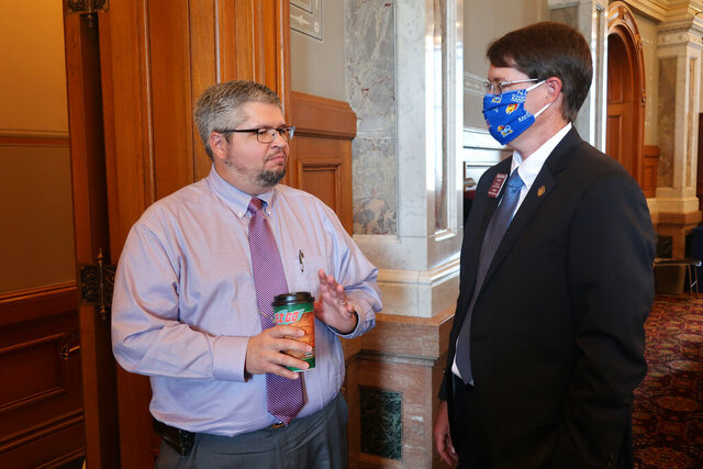 Kansas state Reps. Kyle Hoffman, left, R-Coldwather, and Fred Patton, R-Topeka, confer during a break in the House session, Wednesday, June 3, 2020, at the Statehouse in Topeka, Kan. Patton is chairman of the House Judiciary Committee and has helped draft legislation giving lawmakers oversight of the state's response to the coronavirus pandemic. (AP Photo/John Hanna)