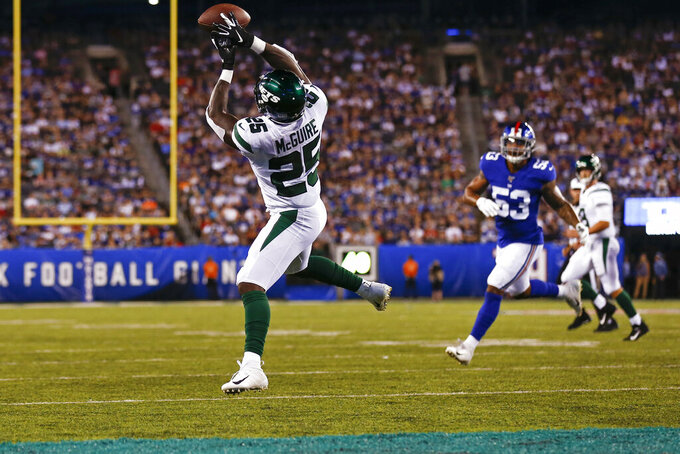 New York Jets running back Elijah McGuire (25) catches a pass for a touchdown in front of New York Giants' Oshane Ximines (53) during the first half of a preseason NFL football game Thursday, Aug. 8, 2019, in East Rutherford, N.J. (AP Photo/Adam Hunger)