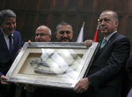 Turkey's President and leader of ruling Justice and Development Party Recep Tayyip Erdogan, right, receives a dagger from supporters as gift as he addresses the members of his ruling party at the parliament in Ankara, Turkey, Tuesday, Feb. 13, 2018. Erdogan issued a warning Tuesday to Greece, Cyprus and international companies exploring for gas in the eastern Mediterranean not to