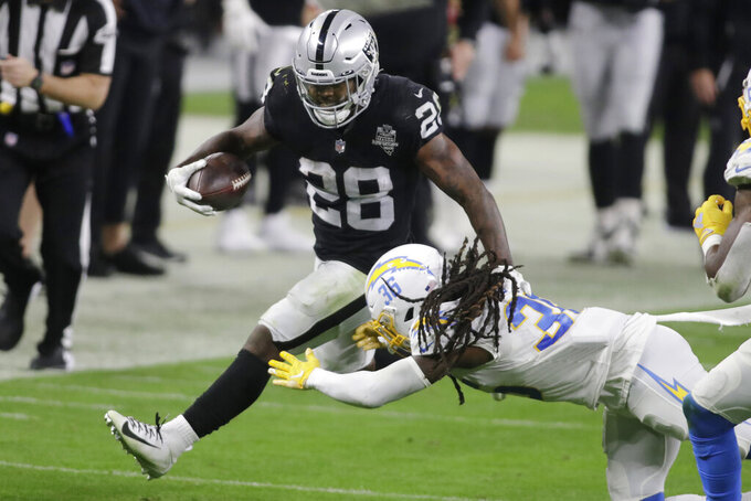 Las Vegas Raiders running back Josh Jacobs (28) runs against Los Angeles Chargers safety Jahleel Addae (36) during the second half of an NFL football game, Thursday, Dec. 17, 2020, in Las Vegas. (AP Photo/Isaac Brekken)