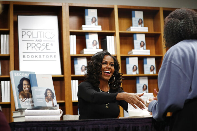 Former first lady Michelle Obama greets people as they buy signed copies of her book,