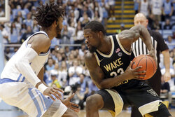 In this March 3, 2020, file photo, Wake Forest's Chaundee Brown (23) works against North Carolina's Leaky Black (1) during the second half of an NCAA college basketball game in Chapel Hill, N.C. Brown says he will enter his name into the NBA draft as well as the NCAA transfer portal. Brown announced his plans in a social-media post Wednesday, April 15, 2020. (AP Photo/Chris Seward, File)