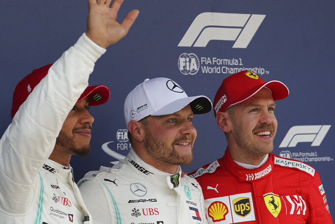 Top three positions after the qualifying session from left Mercedes driver Lewis Hamilton of Britain in second, Mercedes driver Valtteri Bottas of Finland in first and Ferrari driver Sebastian Vettel of Germany in third pose for photos after the qualifying session for the Chinese Formula One Grand Prix at the Shanghai International Circuit in Shanghai on Saturday, April 13, 2019. (AP Photo/Ng Han Guan)