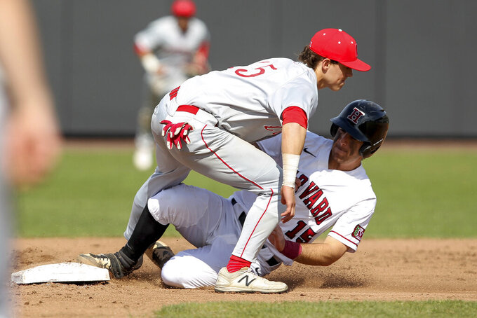 FILE - In this April 13, 2019, file photo, Harvard's Jake Suddleson, right, slides safely into second base ahead of the tag by Cornell's MattCollins, left, during an NCAA college baseball game in Boston. The Ivy League has decided not to allow its spring-sport athletes who had their seasons shortened by the coronavirus pandemic to have an additional year of eligibility, despite the NCAA granting that option earlier this week. The move, which was announced Thursday, April 2, 2020, was consistent for the Ivy League, which hasn't allowed athletes who received medical redshirts to play for a fifth year.(AP Photo/Stew Milne, File)