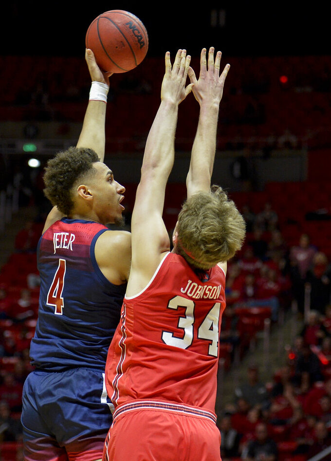 Arizona center Chase Jeter (4) shoots over Utah center Jayce Johnson (34) during the first half of an NCAA college basketball game Thursday, Feb. 14, 2019, in Salt Lake City. (AP Photo/Alex Goodlett)