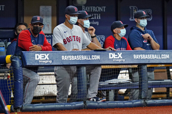 Boston Red Sox manager Alex Cora, left, and other members of the coaching staff wear protective masks during the fourth inning of a baseball game against the Tampa Bay Rays Monday, Aug. 30, 2021, in St. Petersburg, Fla. (AP Photo/Chris O'Meara)