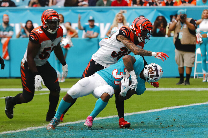 Miami Dolphins running back Myles Gaskin (37) scores a touchdown, as Cincinnati Bengals free safety Jessie Bates (30) attempts to defend, during the second half at an NFL football game, Sunday, Dec. 22, 2019, in Miami Gardens, Fla. To the left is Cincinnati Bengals defensive end Carl Lawson (58). (AP Photo/Brynn Anderson)