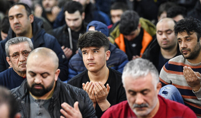Muslim believers pray in a mosque for the victims of the shooting in Hanau, Germany, Friday, Feb. 21, 2020. A 43-year-old German man shot and killed several people of foreign background, most of them Turkish, on Wednesday night in an attack that began at a hookah bar. (AP Photo/Martin Meissner)