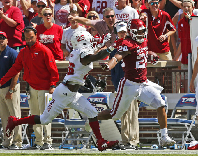 Oklahoma running back Rodney Anderson (24) runs away from Florida Atlantic cornerback Chris Tooley (26) for a touchdown in the first half of an NCAA college football game in Norman, Okla., Saturday, Sept. 1, 2018. (AP Photo/Sue Ogrocki)