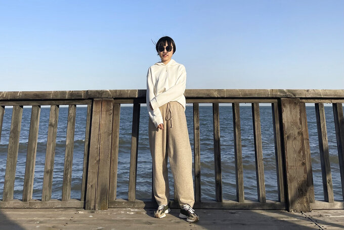 In this April 3, 2021, photo and released by Monica Ma, Monica Ma poses for a photo along the coast of Qinhuangdao in northern China's Hebei province. Ma is among at least 500 students the Chinese government says have been rejected under a policy, aimed at blocking Beijing from obtaining U.S. technology with possible military uses, issued last year by then U.S. President Donald Trump. (Monica Ma via AP)