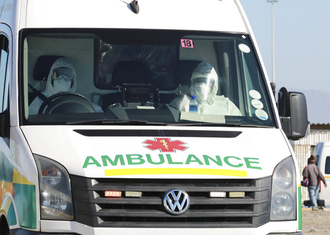 In this photo taken Tuesday, May 19, 2020, paramedics in protective gear drive in an ambulance in Khayelitsha in Cape Town South Africa, With dramatically increased community transmission, Cape Town has become the center of the COVID-19 outbreak in South Africa and the entire continent. (AP Photo/Nardus Engelbrecht)