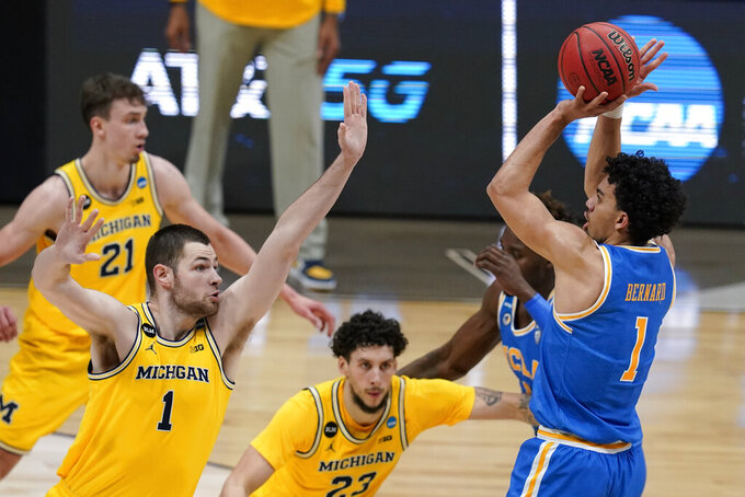 UCLA guard Jules Bernard, right, shoots over Michigan center Hunter Dickinson, left, during the first half of an Elite 8 game in the NCAA men's college basketball tournament at Lucas Oil Stadium, Tuesday, March 30, 2021, in Indianapolis. (AP Photo/Michael Conroy)