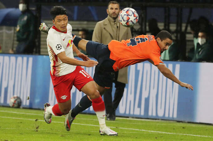 Leipzig's Hwang Hee-chan, left and Basaksehir's Rafael challenge for the ball during a Group H Champions League soccer match between RB Leipzig and Istanbul Basaksehir at the RB Arena in Leipzig, Germany, Tuesday Oct. 20, 2020. (AP Photo/Markus Schreiber)