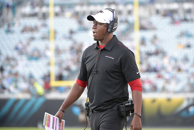 "FILE - In this Aug. 29, 2019, file photo, Atlanta Falcons' Raheem Morris watches from the sideline during the first half of a preseason NFL football game against the Jacksonville Jaguars, in Jacksonville, Fla. Morris is returning to his roots as a defensive coach. The Falcons hope the move will help save their season. After 3½ seasons working with the receivers on the offensive side, Morris is now in charge of the struggling secondary.  ""You do whatever is required for the team,'"" Morris said. (AP Photo/Phelan M. Ebenhack, File)"