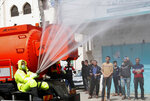 In this March 27, 2020, photo, residents watch workers wearing protective gear spray disinfectant as a precaution against the coronavirus, at the main road of closed market of Shijaiyah neighborhood in Gaza City. Gaza municipality closed all the weekly Friday markets in Gaza starting from today. (AP Photo/Adel Hana)
